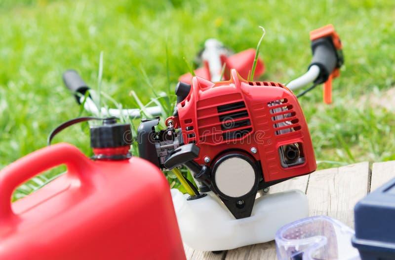 Falciatrice da giardino e scatola metallica rossa con la bugia della benzina su un prato inglese verde immagini stock libere da diritti