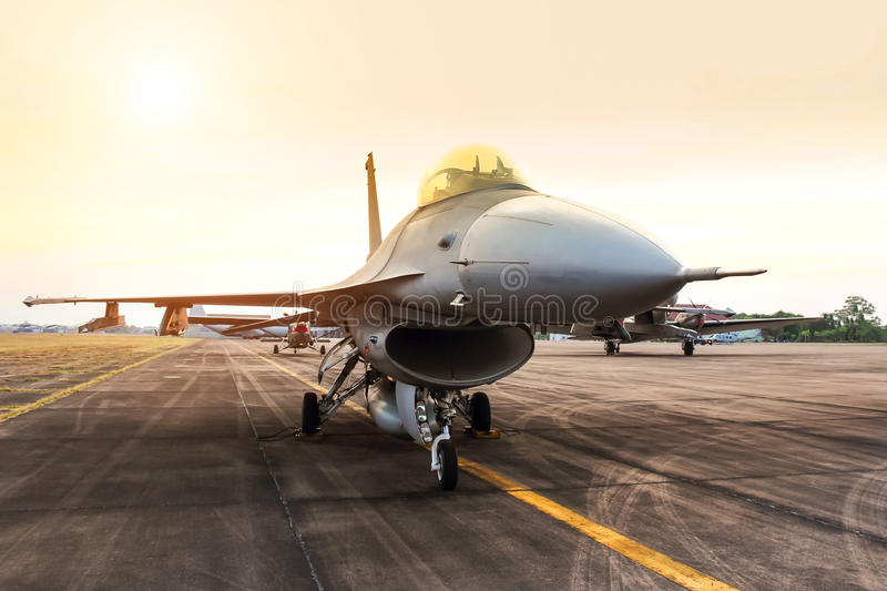 Falcon fighter jet military aircraft parked on runway on sunset. Falcon fighter jet military aircraft parked on runway airforce base on sunset stock photography