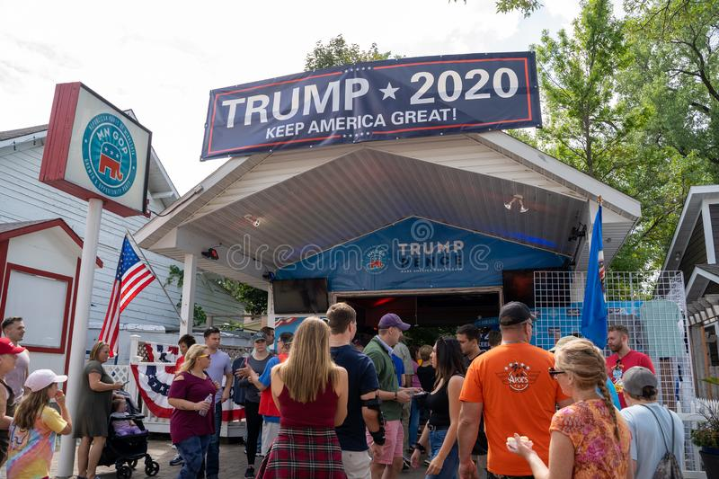 Fairgoers gather around the Trump Pence MN GOP vendor booth in support of President Donald. Falcon Heights, MN - August 25, 2019: Fairgoers gather around the royalty free stock image