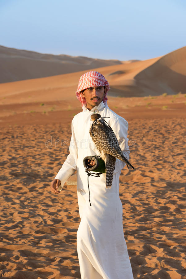 Falconer and falcon man with bird of prey in Abu Dhabi, UAE, United Arab Emirates. Falconer with falcon in desert, man with bird of Prey stock images
