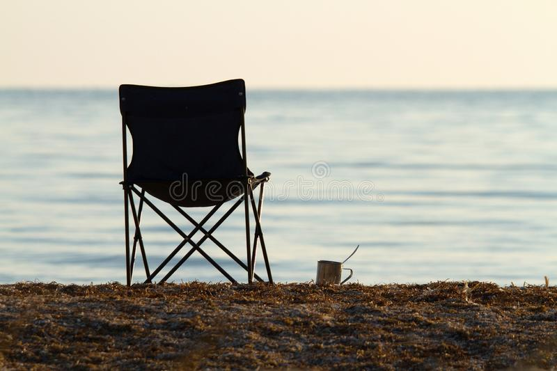 Falcowania turystyczny krzesło i filiżanka na plaży w wczesnym poranku Obrazek dla blogu zdjęcia stock