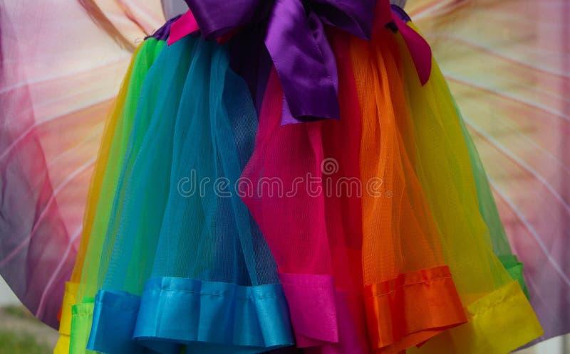 Falda multicolora del satén con los arcos bicolores Una falda de la tela roja, de la naranja, azul, azul, amarilla, verde y rosad fotos de archivo