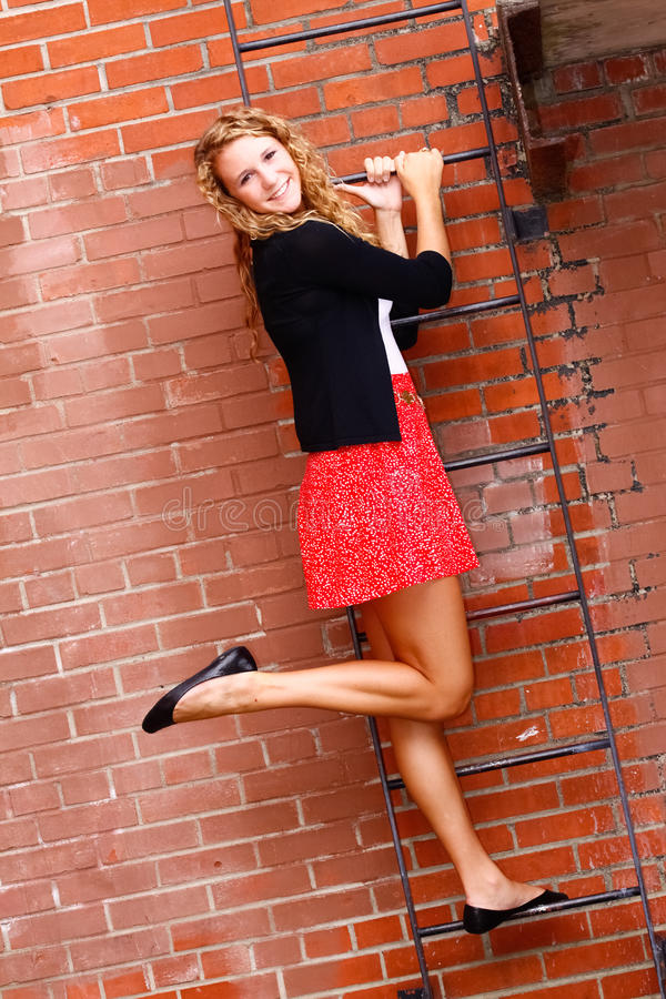 Falda roja de la mujer joven, en escalera de la pared de ladrillo fotografía de archivo