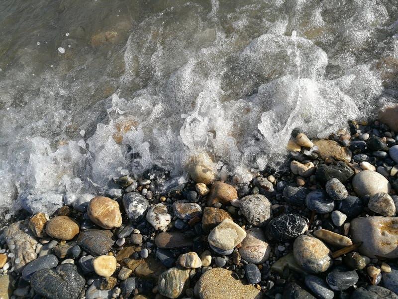 Fale denny chlupot na otoczaków kamieniach na plaży zdjęcie stock