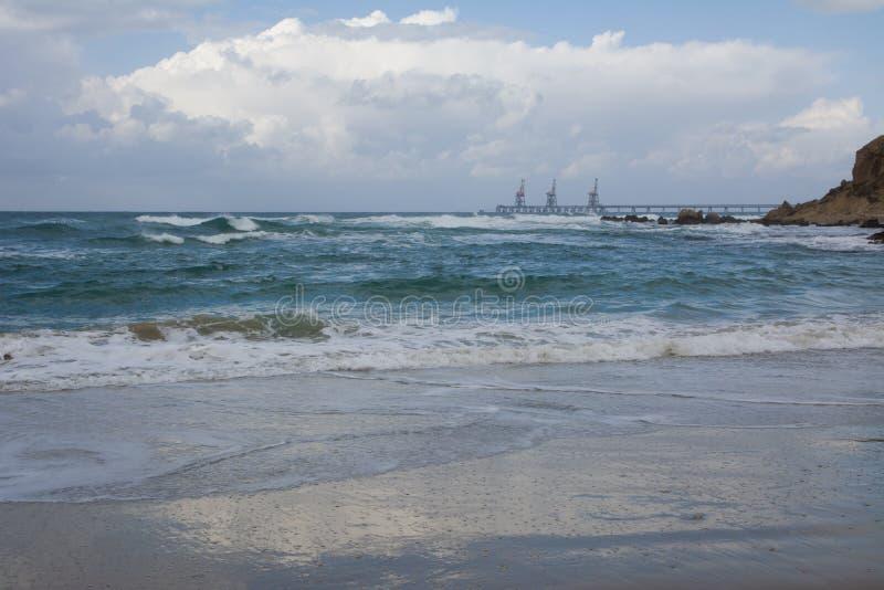 Fale rozbija na linii brzegowej z markotnym dramatycznym niebem obrazy stock