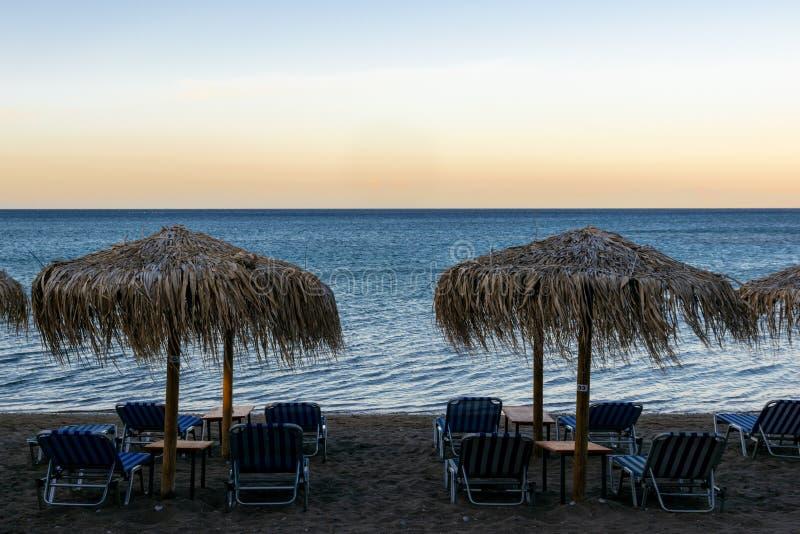 Fale, wiatr na plaży z parasolami i sunbeds, holów krzesła na zmierzchu obrazy stock