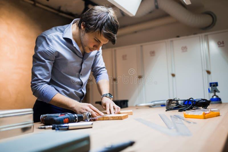 Falegname che lavora e che progetta sul banco da lavoro immagine stock libera da diritti
