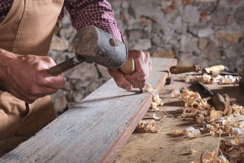 Falegname che per mezzo dello scalpello per lisciare giù legno fotografia stock libera da diritti