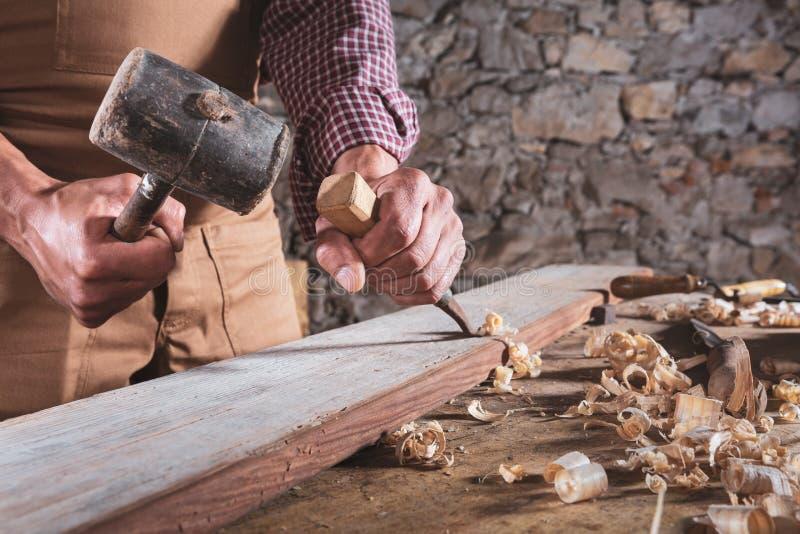 Falegname che per mezzo dello scalpello per lisciare giù legno immagini stock