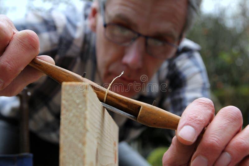 Falegname tradizionale che usando lo spokeshave antico del legno di bosso fotografia stock libera da diritti