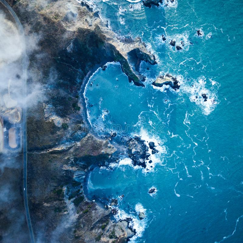 Falezy z skalistymi ścianami patrzeje nad błękitnym falistym oceanem w Kalifornia obraz stock