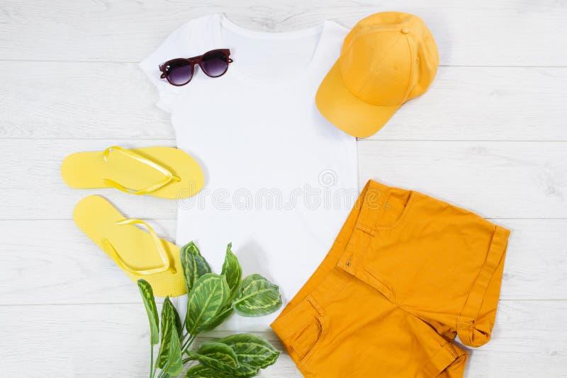 Falhanços de aleta fêmeas brancos da camisa de t trocistas acima da configuração do plano no fundo de madeira Espa?o da vista sup imagens de stock