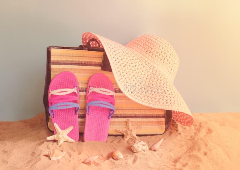 Falhanços de aleta, saco, chapéu do verão e conchas do mar na praia da areia no contexto azul fotografia de stock