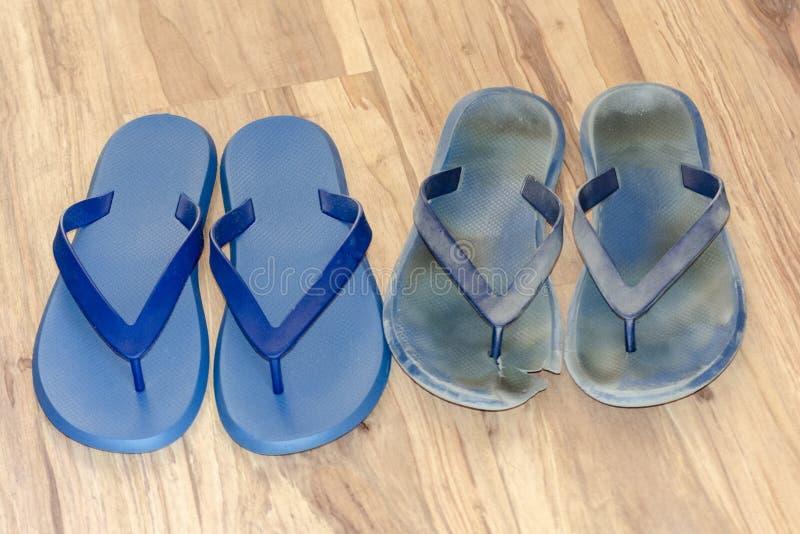 Falhanços de aleta sujos novos e velhos em claro - assoalho marrom Dois pares novos e sapatas gastadas Sandálias azuis no fundo d foto de stock