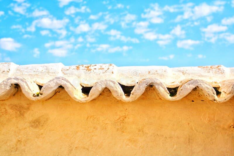Faliste płytki nad adobe ściana z jaskrawym niebieskim niebem obraz royalty free