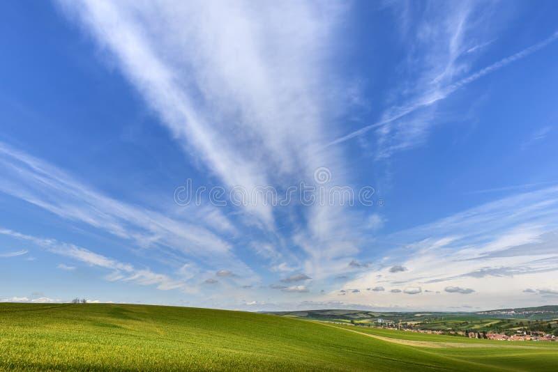 Falisty zieleni pole z chmurnym niebieskim niebem i małą wioską obraz stock
