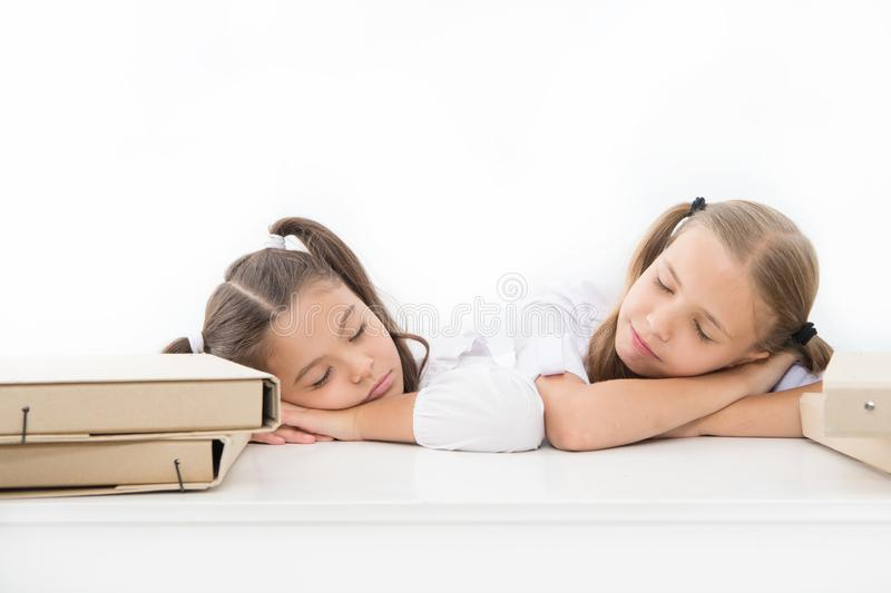 Fall asleep on lesson. Girls fall asleep while work school project white background. Schoolgirls tired of studying. Kids royalty free stock photo