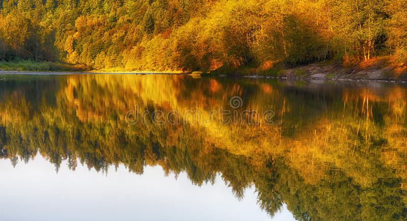 Fall Attire On The Sandy River. Sunlight and reflecting fall colors along the Sandy River near Gresham, Oregon stock image