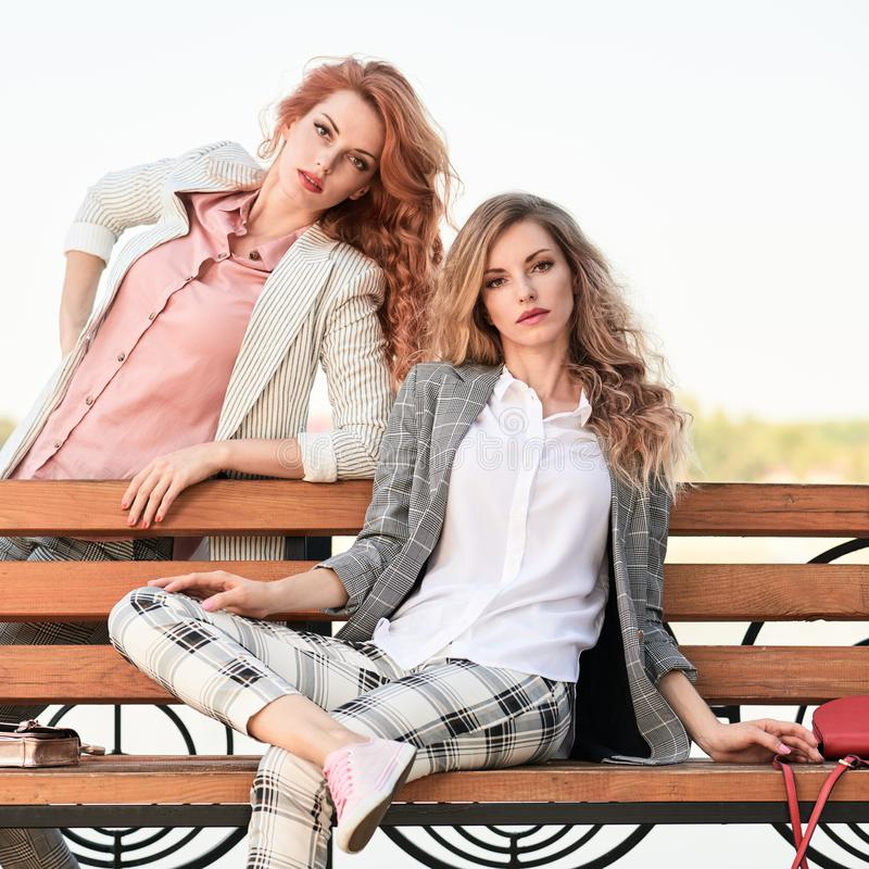 Fall Fashion Outdoor. Woman in Autumn outfit beach. Fall autumn outdoor. Fashionable adorable women posing on the bench. Two Beautiful Blonde Redhead lady in stock photography