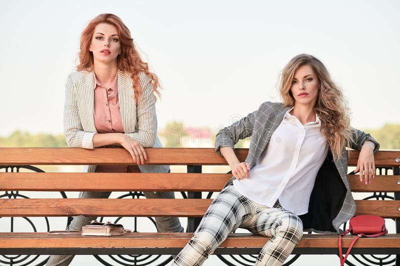 Fall Fashion Outdoor. Woman in Autumn outfit beach. Fall autumn outdoor. Fashionable adorable women posing on the bench. Two Beautiful Blonde Redhead lady in royalty free stock photos