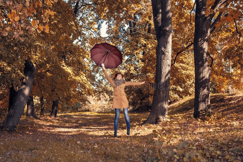 Fall. Autumn Park. Autumnal Trees and Leaves in sun rays. redhead girl with umbrella enjoying in nature stock photo