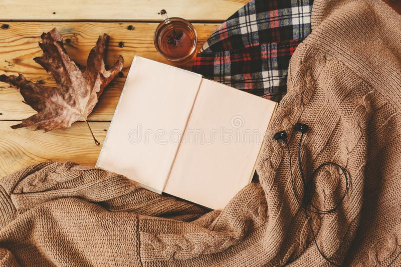 Fall background. Opened book, fall leaf and knitted sweater. A cup of hot tea, knitted scarf on wooden table. Autumn warming drink. Top view. Copy space stock photos