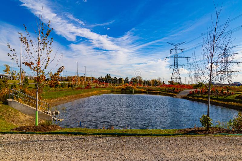 Fall in the city; Fall foliage colors surrounding a lake. Power Lines over foliage. Fall beautiful foliage colors around a lake with a trail and beautiful blue stock photography