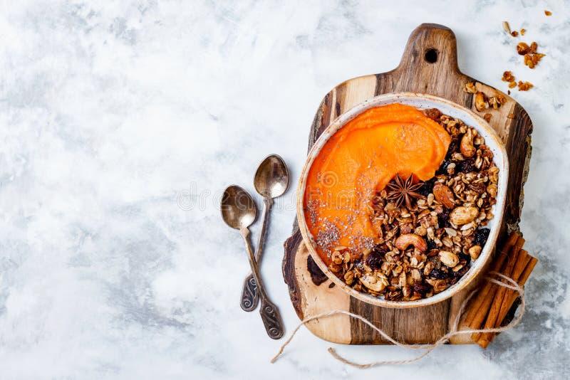 Fall breakfast bowl with cinnamon granola, coconut yogurt, chia seeds and pumpkin puree. Healthy vegan, vegetarian autumn smoothie. Bowl royalty free stock photo