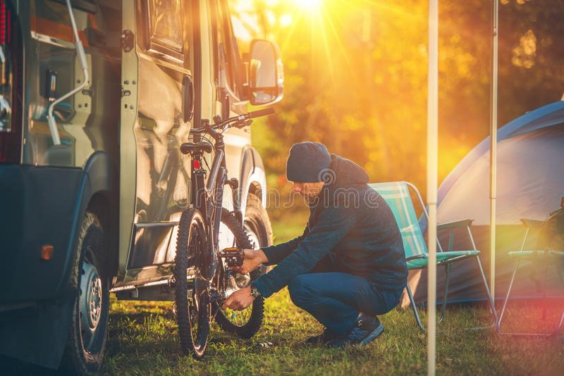 Fall Camping Time. Motorhome and Tent Camping. Men Preparing His Mountain Bike For a Trip royalty free stock photography