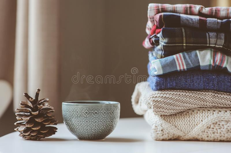 Fall casual woman fashion clothes set. Stack of plaid shirts and knitted sweaters with pine cone and cup of tea. Cozy stylish womanswear and hygge concept royalty free stock photo