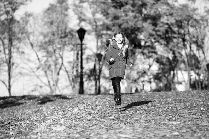 Fall clothes and fashion concept. Child blonde long hair walking fall park background. Feel cozy in warm jacket. Girl. Happy wear coat with hood enjoy fall stock image