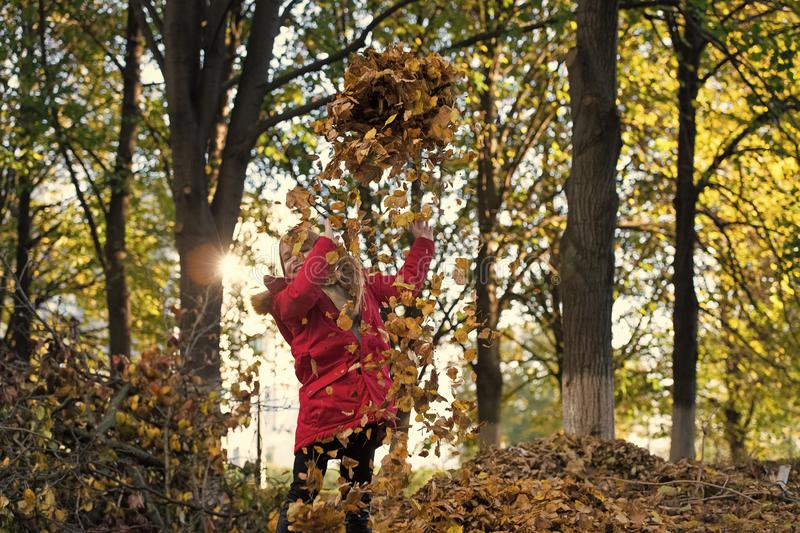 Fall clothes and fashion concept. Child blonde long hair walking fall park background. Girl happy wear coat with hood. Enjoy fall nature. Child wear coat for royalty free stock photography