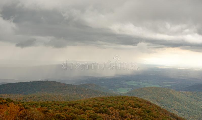 Fall color forest and rolling hills and valleys in the Appalachians of Virginia with rain and clouds in the distance. On Skyline Drive stock images