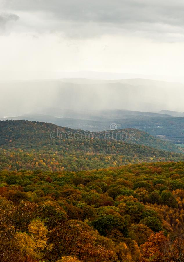 Fall color forest and rolling hills and valleys in the Appalachians of Virginia with rain and clouds in the distance. On Skyline Drive stock photo