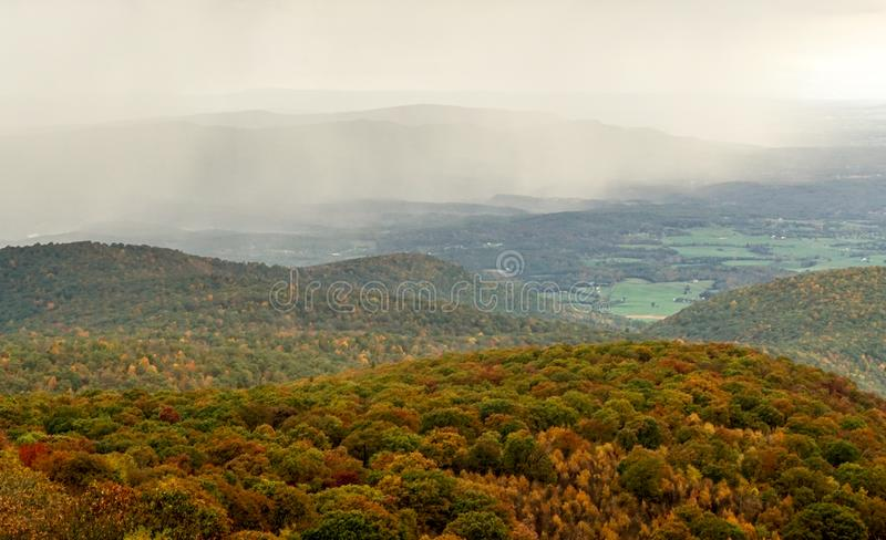 Fall color forest and rolling hills and valleys in the Appalachians of Virginia with rain and clouds in the distance. On Skyline Drive royalty free stock image
