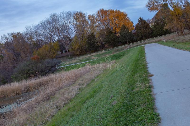 Fall colors along a paved path in a park. Lake Zorinsky in Omaha Nebraska. Beautiful cloud and skyline royalty free stock photography