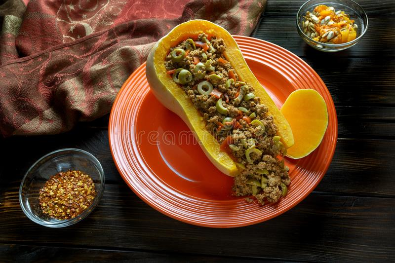 Fall colors with Butternut Squash Boat filled with ground beef with sliced olives on a red plate with some red pepper flakes on t. He side for a spicy kick on a stock photography