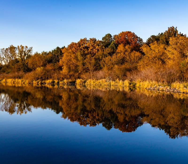 Fall colors in a park with reflections in the lake in Omaha Nebraska. View of fall colors in a park at sunset with reflections in the lake in Omaha Nebraska stock photos