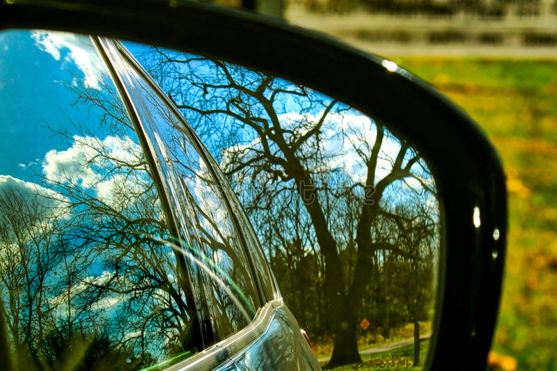 Fall colors are reflected in a rearview mirror of a car parked in an Indiana forest. A rearview mirror reflects the beauty of a rural autumn scene in Indiana royalty free stock image