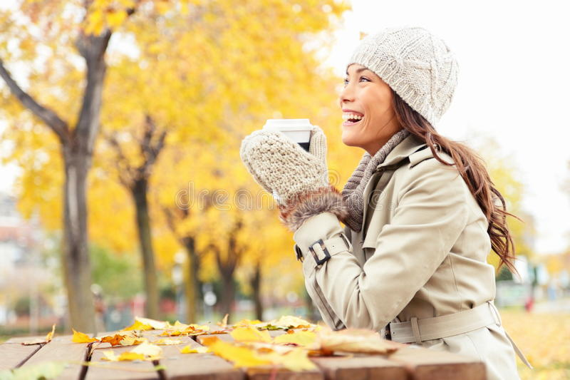 Fall concept - autumn woman drinking coffee. On park bench under fall foliage. Beautiful young modern woman smiling happy and cheerful in trench coat royalty free stock photography