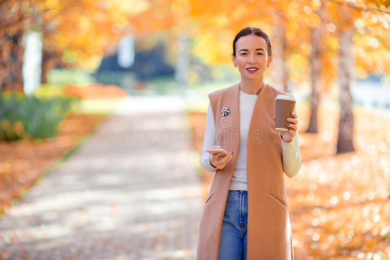 Fall concept - beautiful woman drinking coffee in autumn park under fall foliage royalty free stock images