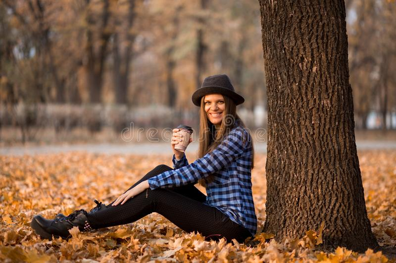 Fall concept. Happy and cheerful woman in hat, drinking coffee while sitting on park leaves royalty free stock photography