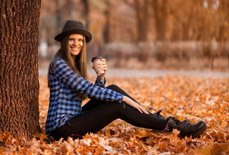 Fall concept. Happy and cheerful woman in hat, drinking coffee while sitting on park leaves stock image