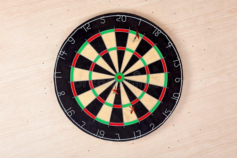 Fall de la blanco Tres flechas no est?n en el centro de los dardos en fondo de madera ligero, no golpean el objetivo Concepto par foto de archivo