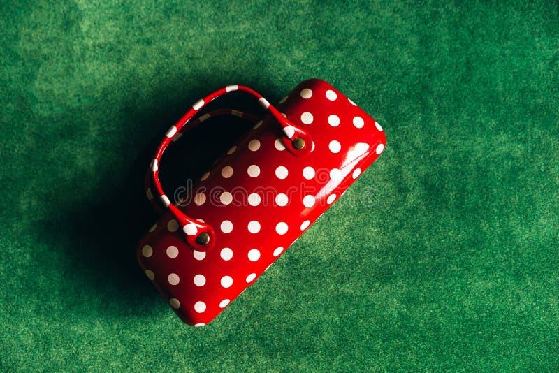 Fall för exponeringsglas i form av kvinnors handväska som är röd med vita prickar arkivfoton