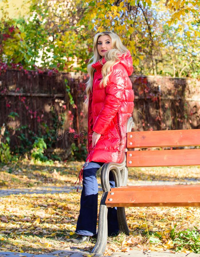 Fall fashion concept. Lady attractive posing in jacket near bench. Woman fashionable blonde with makeup stand in. Autumnal park. Jacket for fall season concept stock photo