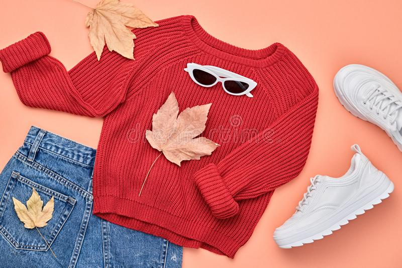 Autumn Fashion Clothes Outfit Flat lay. Maple Leaf. Fall fashion Flat lay. Trendy red jumper, Stylish hipster sneakers, sunglasses, denim, autumn Maple Leaf stock photography
