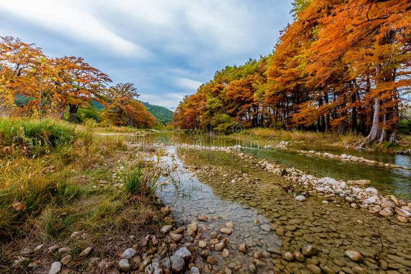 Fall Foliage Surrounding the Cobble Stoned Frio River. Beautiful Fall Foliage Surrounding the Clear and Cobble Stoned Frio River, Texas on a Cloudy Day royalty free stock photography