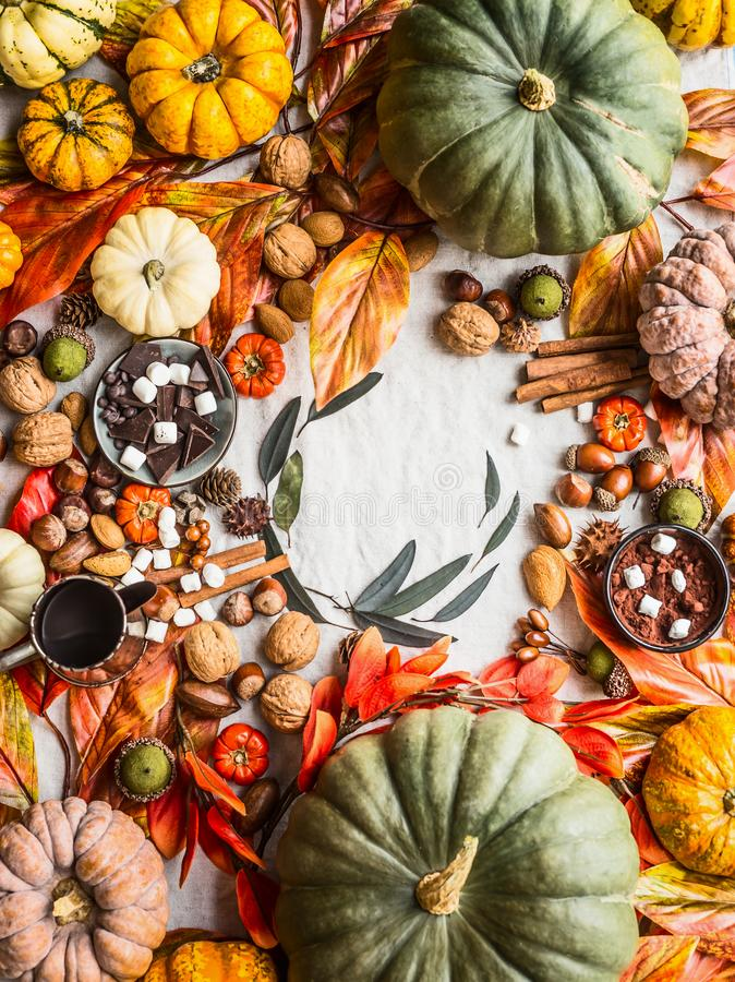 Fall food background with variety of colorful pumpkins , chocolate, spices, marshmallow, nuts and autumn leaves, top view. Autumn stock photography