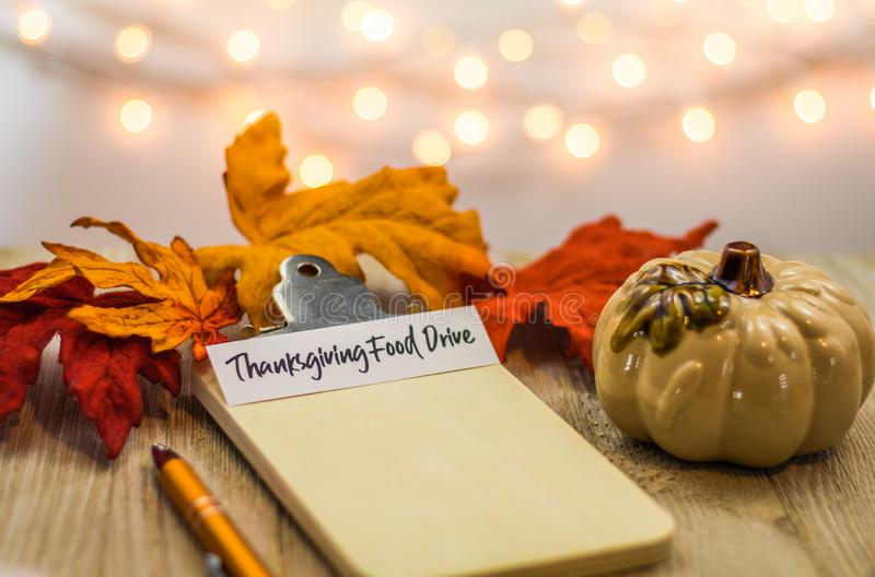 Thanksgiving Food Drive list concept on blank clipboard surrounded with bright leaves and decorative items soft background. Fall Food Drive list concept on blank stock photos